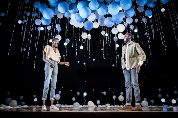 A female and male figure standing on stage with white and blue balloons floating above them.