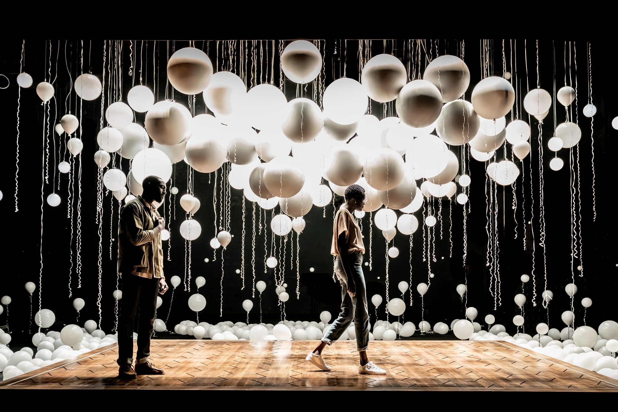 Two figures on a stage with white balloons floating above them